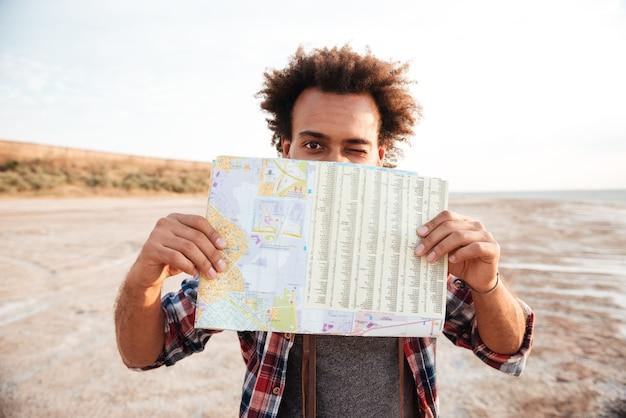 Радостный афро-американский молодой человек закрыл лицо картой и подмигнул