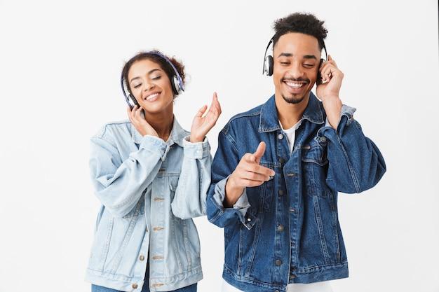 Радостная африканская пара в джинсовых рубашках слушает музыку вместе в наушниках с закрытыми глазами на серой стене