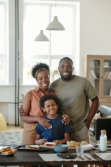 Joyful african family consisting of mother, father and cute little son standing by kitchen table in front of camera in home environment