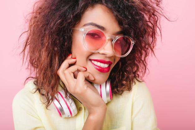 彼女の顔に触れて、笑顔の赤い唇を持つうれしそうなアフリカの女性モデル。サングラスとヘッドフォンで喜んで笑っている愛らしい巻き毛の女性のクローズアップの肖像画。