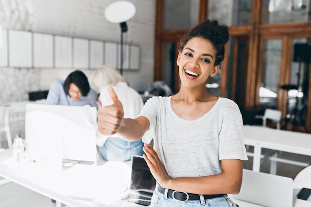 Gioiosa studentessa africana con acconciatura corta, alzando il pollice dopo aver superato gli esami. ritratto di donna nera felice in maglietta grigia divertendosi in ufficio mentre i suoi colleghi lavorano al progetto.