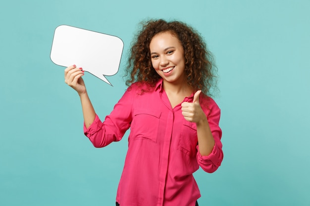 Joyful african girl in casual clothes hold empty blank say cloud, speech bubble, showing thumb up isolated on blue turquoise background. people sincere emotions lifestyle concept. mock up copy space.