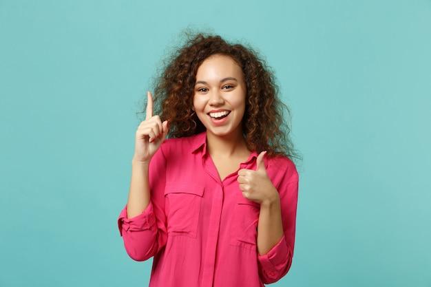 Gioiosa ragazza africana in abiti casual tenendo il dito indice in alto con una grande nuova idea che mostra pollice in su isolato su sfondo blu turchese. concetto di stile di vita di emozioni sincere della gente. mock up copia spazio.