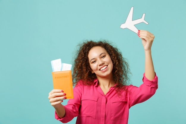 Joyful african girl in casual clothes holding passport, boarding pass ticket, paper airplane isolated on blue turquoise wall background. people sincere emotions lifestyle concept. mock up copy space.