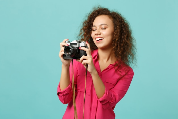 Joyful african girl in casual clothes taking picture on retro vintage photo camera isolated on blue turquoise wall background in studio. people sincere emotions lifestyle concept. mock up copy space.