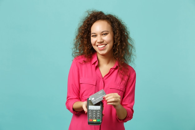 Joyful african girl hold wireless modern bank payment terminal to process, acquire credit card payments isolated on blue turquoise background. people emotions, lifestyle concept. mock up copy space.