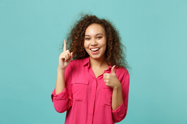 青いターコイズブルーの背景に分離された親指を示す素晴らしい新しいアイデアで人差し指を保持しているカジュアルな服を着たうれしそうなアフリカの女の子。人々の誠実な感情のライフスタイルの概念。コピースペースをモックアップします。