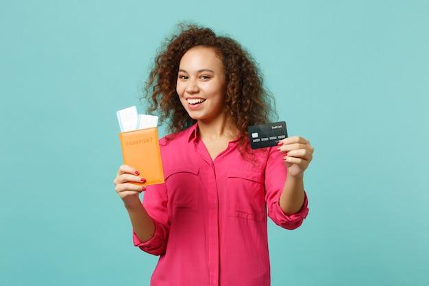 파란색 청록색 벽 배경에 격리된 여권 탑승권 신용 은행 카드를 들고 평상복을 입은 즐거운 아프리카 소녀. 사람들은 진심 어린 감정 라이프 스타일 개념입니다. 복사 공간을 비웃습니다.