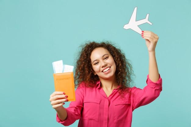 여권, 탑승권, 파란색 청록색 벽 배경에 격리된 종이 비행기를 들고 평상복을 입은 즐거운 아프리카 소녀. 사람들은 진심 어린 감정 라이프 스타일 개념입니다. 복사 공간을 비웃습니다.