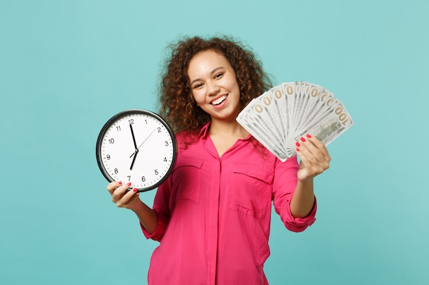 Joyful african girl in pink clothes hold round clock fan of money in dollar banknotes cash money isolated on blue turquoise background. people sincere emotions, lifestyle concept. mock up copy space.