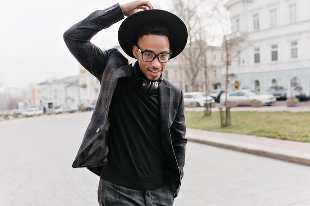 ヘッドフォンで公園を歩いているカジュアルな服装でうれしそうなアフリカ人。屋外で朝を過ごし、人生を楽しんでいる帽子に興味のある黒人の男。