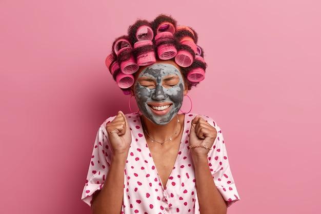 Gioiosa donna afroamericana stringe i pugni, attende un bell'effetto della maschera all'argilla, chiude gli occhi e sorride ampiamente, applica i bigodini, si veste casualmente, posa