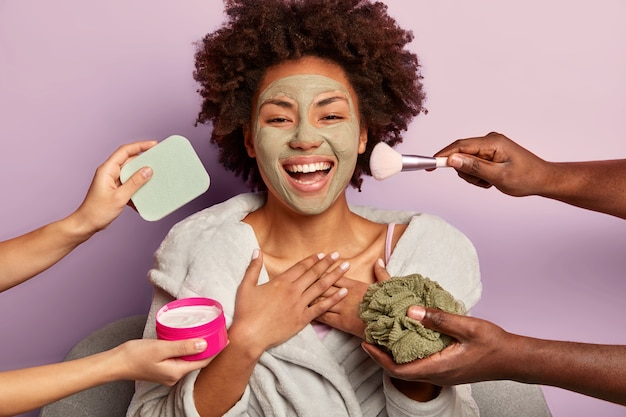 Joyful afro american woman laughs sincerely, applies peeling mask, gets different beauty treatments at same time
