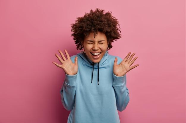 うれしそうなアフロアメリカ人女性は手のひらを上げ、明るい感じ、素晴らしいニュースを喜ぶ