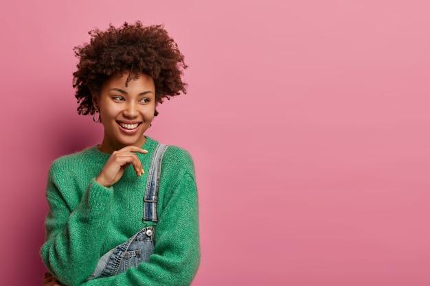 うれしそうなアフロアメリカ人女性はあごに触れ、楽しく笑い、機嫌が良い