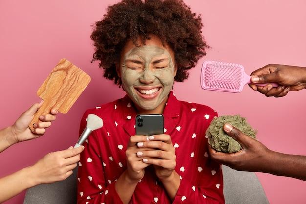 즐거운 아프리카 계 미국인 여성이 휴대 전화를 사용하고, 온라인에서 뷰티 블로그를 읽고, 넓게 웃으며, 천연 클레이 마스크를 바르고, 잠옷을 입습니다.
