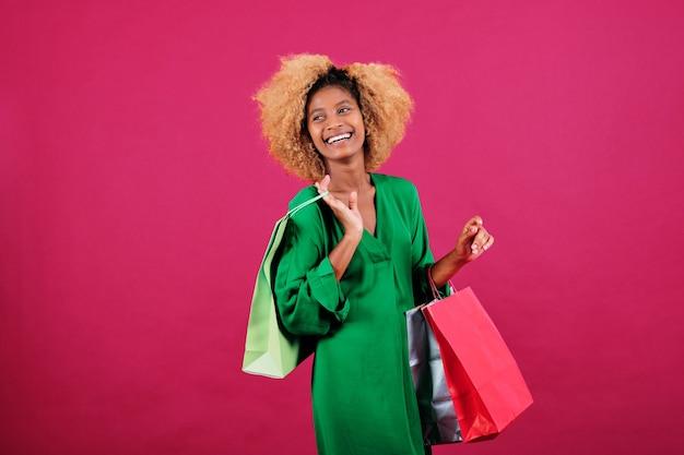Радостная афро женщина, держащая красочные бумажные пакеты, стоя на изолированном фоне. черная пятница продажа и концепция покупок.