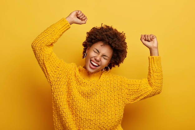 Joyful afro woman raises arms, tilts head, dressed in casual knitted jumper, laughs from happiness, celebrates victory, isolated on yellow