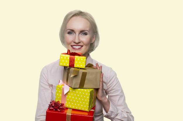 Joyful american woman is holding many gift boxes