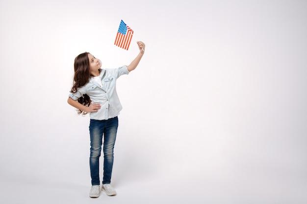 Радостная забавная милая девушка держит американский флаг, выражая позитив, стоя изолированной в белой стене