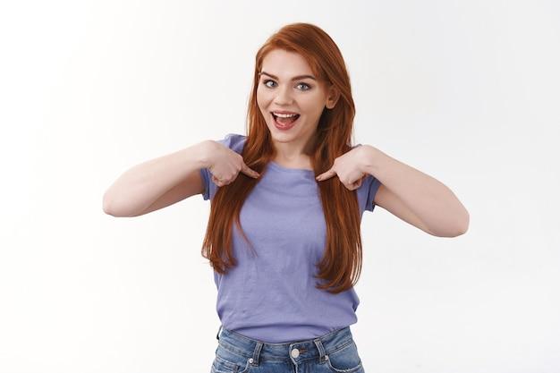 보라색 티셔츠를 입은 즐거운 웃고 있는 빨간 머리 백인 여성, 가슴을 가리키며 웃으면서 개인적인 성취를 말하고, 자랑하고, 자원하고, 후보 제안, 흰 벽