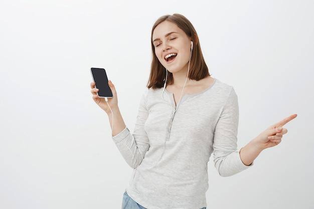 Радостная и восторженная красивая европейская женщина с каштановой стрижкой, закрывающая глаза, уводящая от веселья и радости, слушая музыку в наушниках, держа смартфон над серой стеной