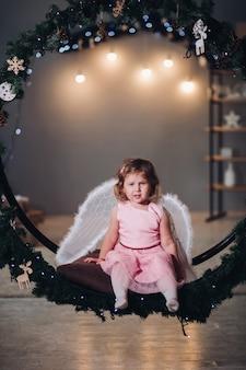 明るい花輪で飾られたモミの花輪に座ってポーズをとって楽しくて幸せな子供。かわいいバラのドレスを着て、後ろに天使の羽を持っている愛らしい女の子。笑顔でカメラを見ている子供。