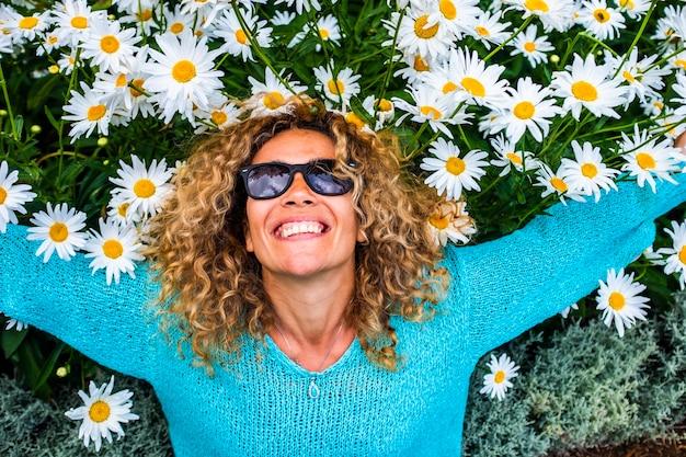 陽気な若い白人女性との喜びと心の概念は、地面に自然の花の表面に横たわっています