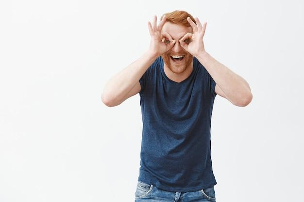 双眼鏡で見ているように、目の上でゼロまたは大丈夫なジェスチャーを示し、幸せそうに笑って見つめ、楽しんでいる、毛のある楽しくて遊び心のある感情的な赤毛の男