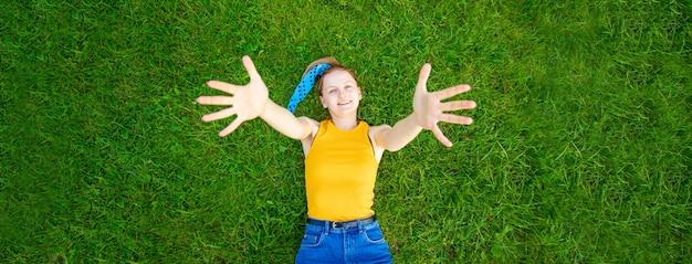 잔디에 즐겁고 웃는 소녀 거짓말 공원에서 외부 카메라를 찾습니다