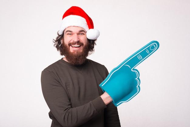 팬 장갑으로 가리키고 산타 클로스 모자를 쓰고 수염을 가진 즐겁고 웃는 남자