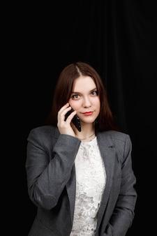 즐겁고 성공적인 젊은 패션 블로거가 감정적으로 전화로 이야기하고 있습니다. 캐주얼 회색 재킷에 아름 다운 젊은 여자는 스마트 폰 들고있다.
