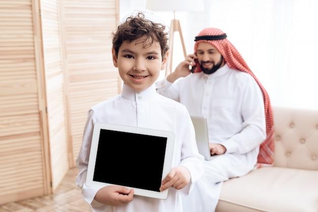 Joyful arab boy presents a new black tablet