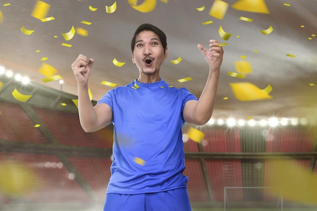 Joyful asian football player man with excited expression