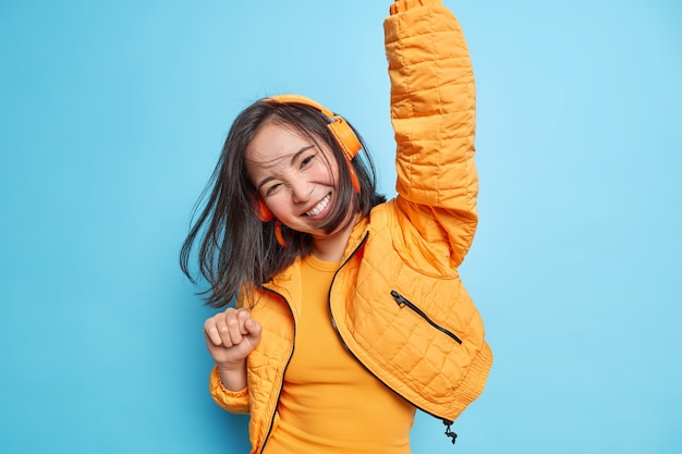 Joyful asian girl has fun dark hair floaring in air while jumping keeps arms raised wears wireless headphones listens music feels energetic isolated over blue wall. people lifestyle happiness