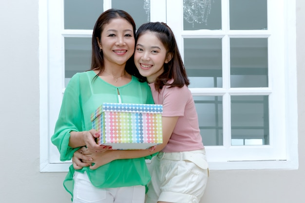 Joyful asian mother and teenage daughter holding gift box