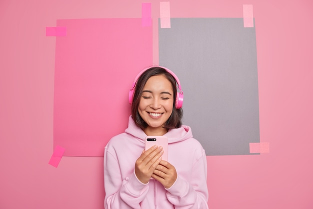 Joyful asian teenage girl uses mobile phone application for listening music wears stereo headphones on ears enjoys relaxing song after studying.