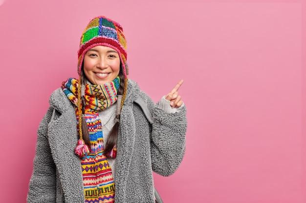 La donna asiatica gioiosa si veste per il freddo invernale indica che uno spazio vuoto mostra qualcosa di fantastico che indossa una pelliccia di cappello lavorato a maglia e una sciarpa intorno al collo isolato sopra il muro rosa