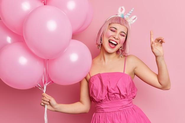 Радостная азиатская женщина наклоняет голову, поднимает руку, чувствует себя очень счастливой на вечеринке