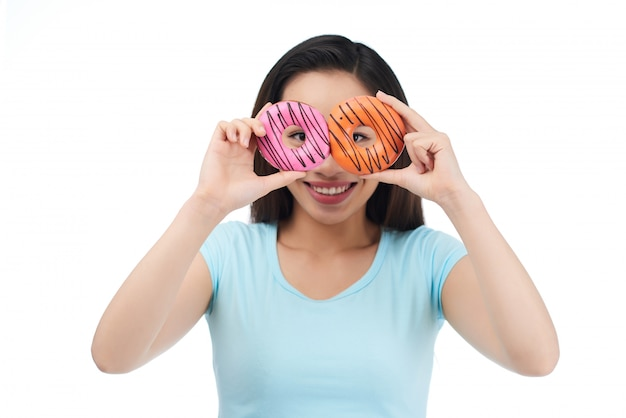 Joyful asian woman with appetizing doughnuts