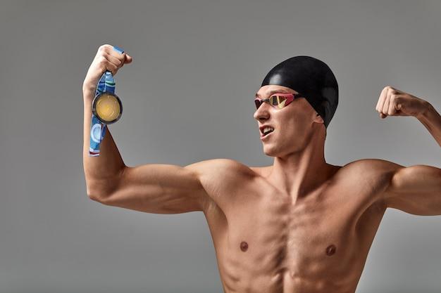 메달을 손에 들고 즐거운 수영 선수는 긍정적인 감정, 승리의 기쁨, 성공의 개념, 결코 포기하지 않고 성공을 달성할 것입니다.