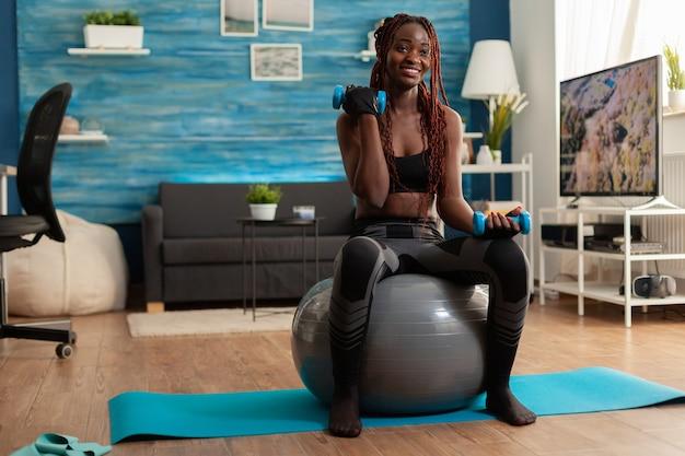 上腕二頭筋のトレーニングにスタビリティボールを使用し、ダンベルでカールをしているレギンスの楽しいアスリート黒人。のための近代的な機器を使用して自宅でスポーツをしている強い運動選手