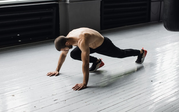 Joyful athletic man doing exercise with pushup while working out