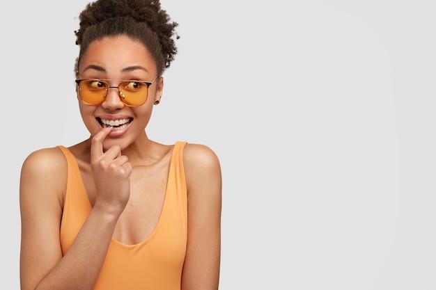 Радостная привлекательная черная женщина с вьющимися волосами