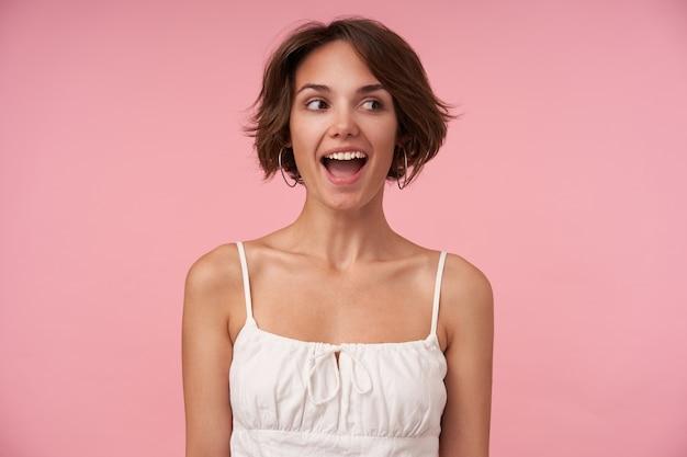 Gioiosa attraente donna bruna con taglio di capelli corto che osserva da parte con un ampio sorriso felice, tenendo le mani lungo il suo corpo, in posa, essendo in alto spirito