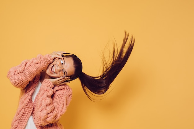 Joyful attractive brunette in glasses and headphones dressed in pink sweater white blouse shakes her head with long flowing hair while dancing, over yellow background. positive people concept.