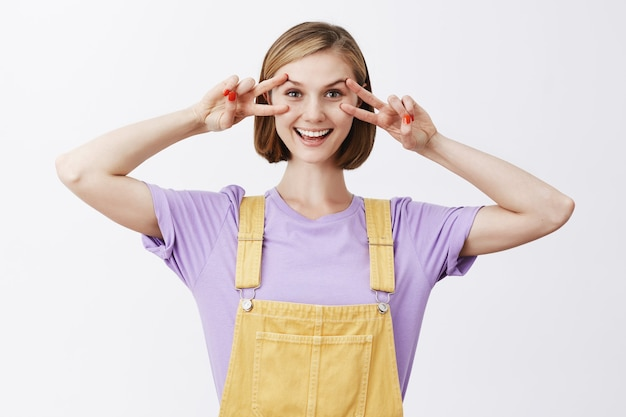 Joyful attractive caucasian girl making peace signs over eyes and smiling joyfully