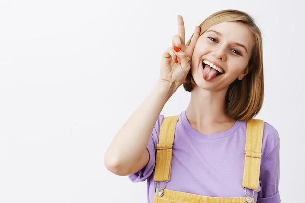 Gioiosa attraente ragazza caucasica facendo segni di pace sugli occhi e sorridendo con gioia