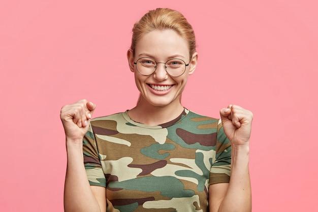 ポジティブな表情のうれしそうな魅力的な女性は、拳で手を上げたまま、心地よく笑顔で、眼鏡をかけ、ピンクのスタジオで隔離