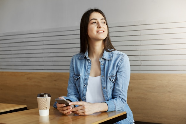 Joyful attractive girl with dark hair sitting in cafe, drinks coffee and chatting with friend on smartphone then turning head to see boyfriend through window.